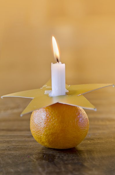tangerine candle holder: candle with golden star in a tangerine