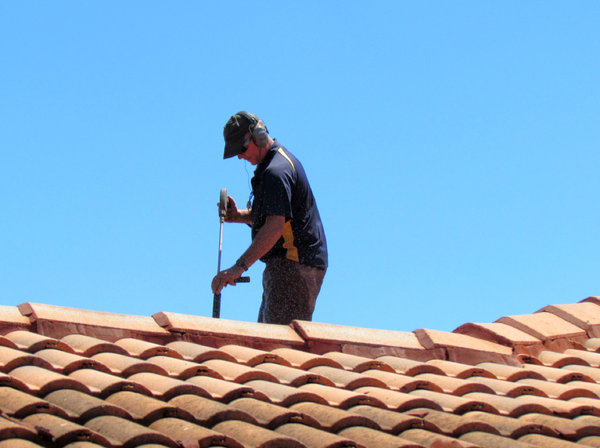 roof restoration1: workman cleaning roof tiles for restoration