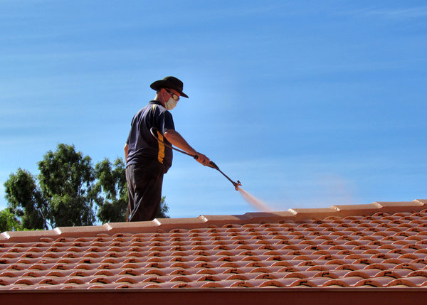 roof restoration12: workman cleaning and painting roof tiles for restoration