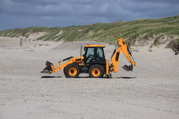 Digger: Digger on the beach working in the line of coast protection