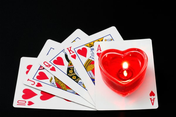 Royal Flush: Royal flush poker cards isolated on a black background, with a lit heart-shaped candle added in for good measure.