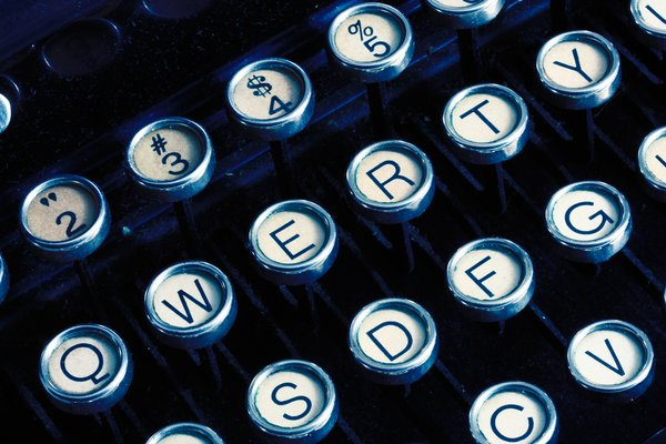 Antique Typewriter Close-up: Close-up of an antique qwerty-format typewriter with blue color tinting.