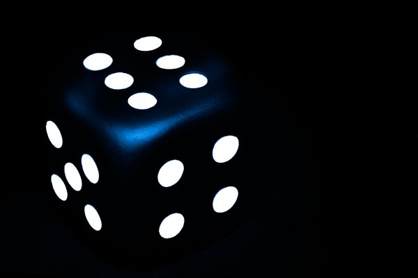 Dark Blue Dice: Close-up of a dice illuminated with a flash light.