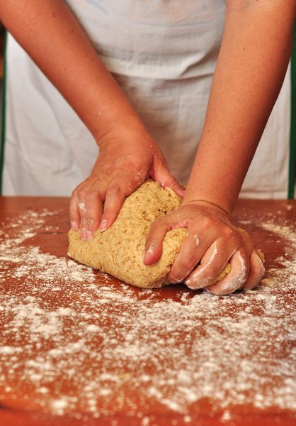 Kneading Pizza dough: Woman kneading whole-wheat pizza dough on a wooden table