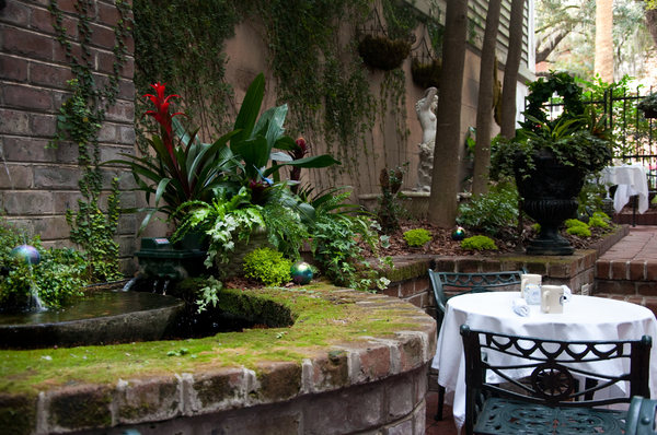 Courtyard table: Dinner for two in a romantic lush grecian courtyard, shot in cloudy weather so the green would appear verdant.