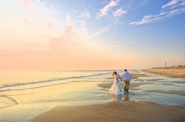 After the Sunrise Wedding: couple leaving the wedding ceremony, just after sunrise, on the beach