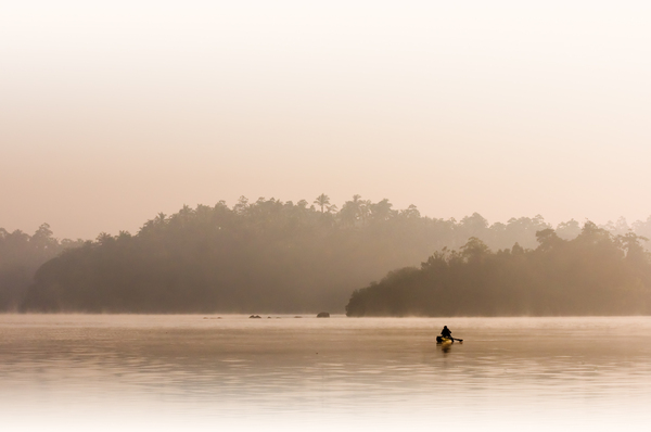 Fisherman in first Morning Lig: Fisherman with Canoe at Sunrise - Kumarakanda Lagoon, Sri Lanka. Misty Atmosphere.