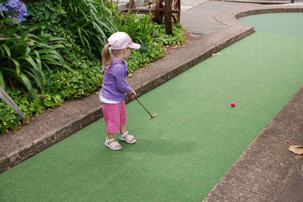 Mini golf: Young girl playing mini golf