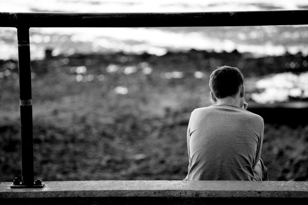 Looking At The Sea: Young man sitting looking out to sea