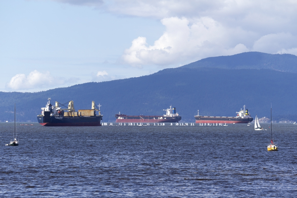 Big and little ships: Tiny dinghys and enormous tankers in a bay of Vancouver, Canada.