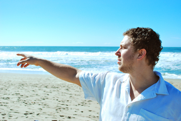 Man Points on the Beach: A man in a white shirt is standing on a beach pointing to the side with waves crashing in the background.