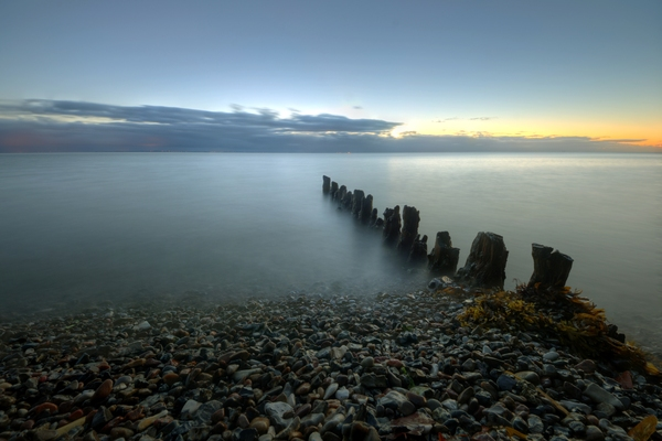 Wooden breakwater - HDR: Old wooden breakwater -looking like bad teeth- in very early morning ligth. The image is HDR.