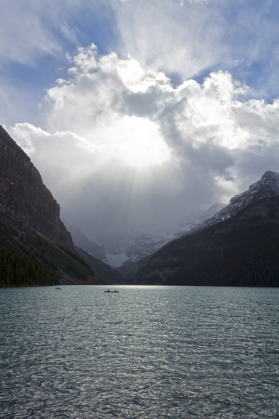 Radiant storm cloud over lake: Stormy cloud and sunlight above some vulnerable-looking canoeists on Lake Louise, Canada.