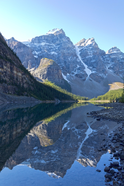 Mountain reflections: Mountains reflected in Lake Moraine, an intensely blue lake of glacial meltwater in western Canada.