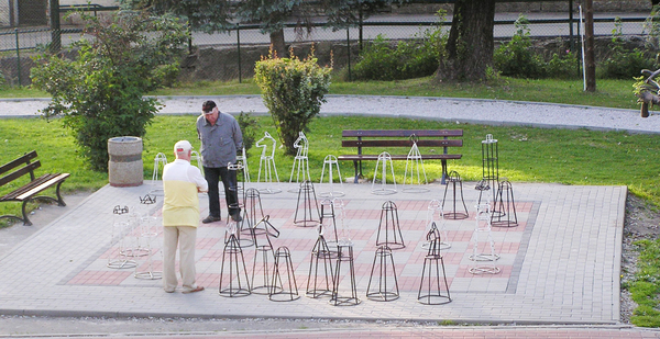 Chess outdoors: Old people playing chess on the street.