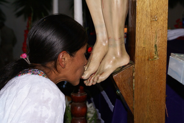 Piety: Indian woman paying homage to the Lord Jesus on the cross.