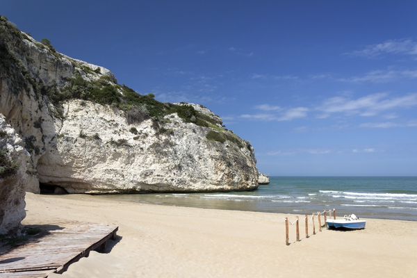Beach, cliff and cave: A beach and chalk cliffs in southern Italy.
