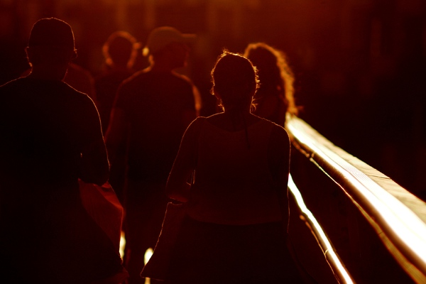 People walking in sunset: People walking across a bridge in sunset light