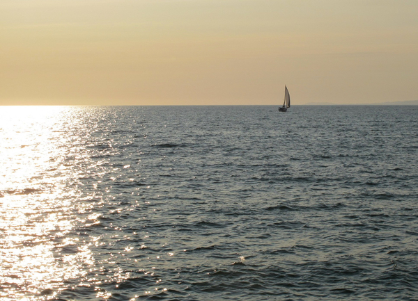 Lonely sailboat: A sailboat just visible in the distance, sailing away from brilliant light reflected in the ocean.