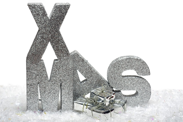 XMAS gifts: Letters spelling XMAS in decoration snow with silver gifts
