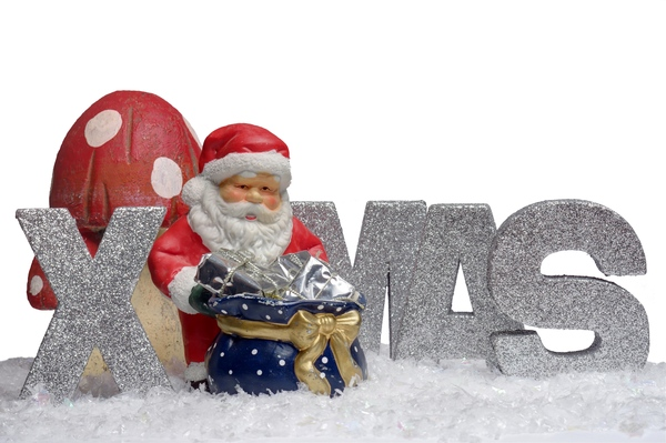XMAS santa with gifts: Letters spelling XMAS and figurine of Santa with a sackfull gifts.