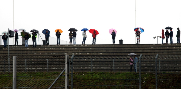 Watching: People in the rain watching an outdoor sport event in the rain