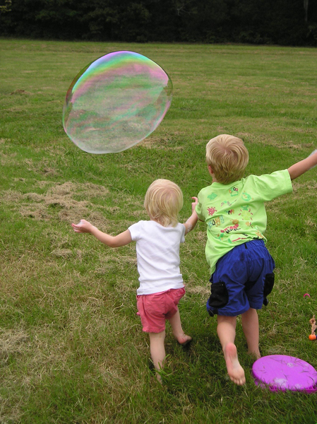 Kids chase a bubble at a famil: Two children, brother and sister, chase a huge bubble in a park. (Please share any comments and/or use of this image ... thanks! :)