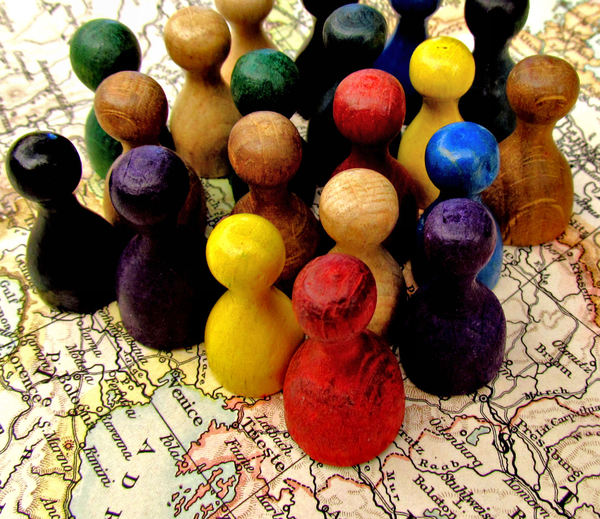 all together3b: game pieces on world map symbolizing togetherness - mixed community