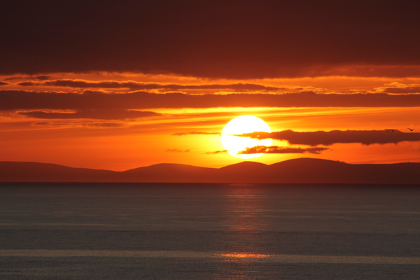 Sunset with Hills: Sun going down over the wee village of Portknockie and the North Sea will hills in the background.